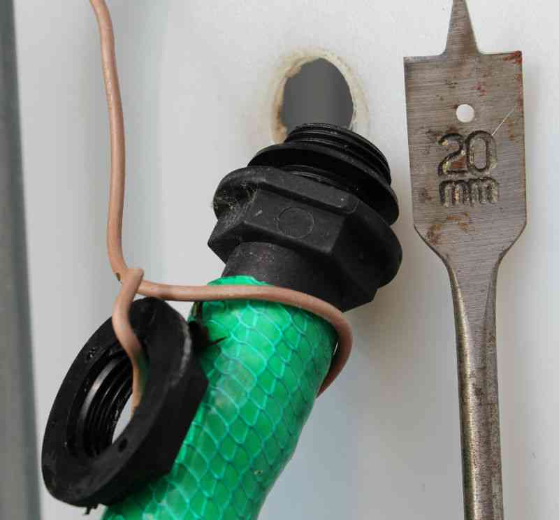 Slangestuds med pakning, omløber (som skrues på indvendig) og et 20 mm fladbor/spadebor til at bore hul i palletank