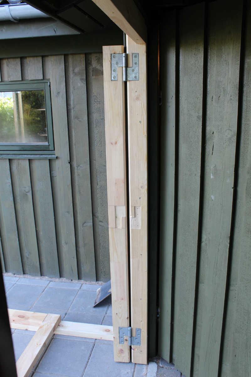 Hængselled af reglar skruet fast på stolpe