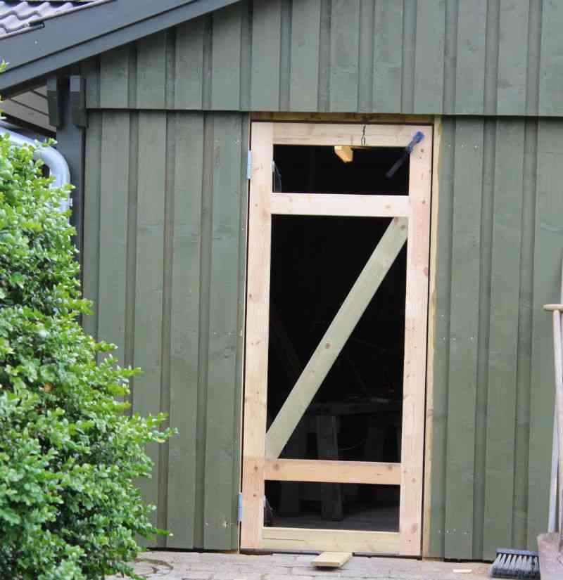 Dørramme på dør til skur nu forsynet med skrå afstivning