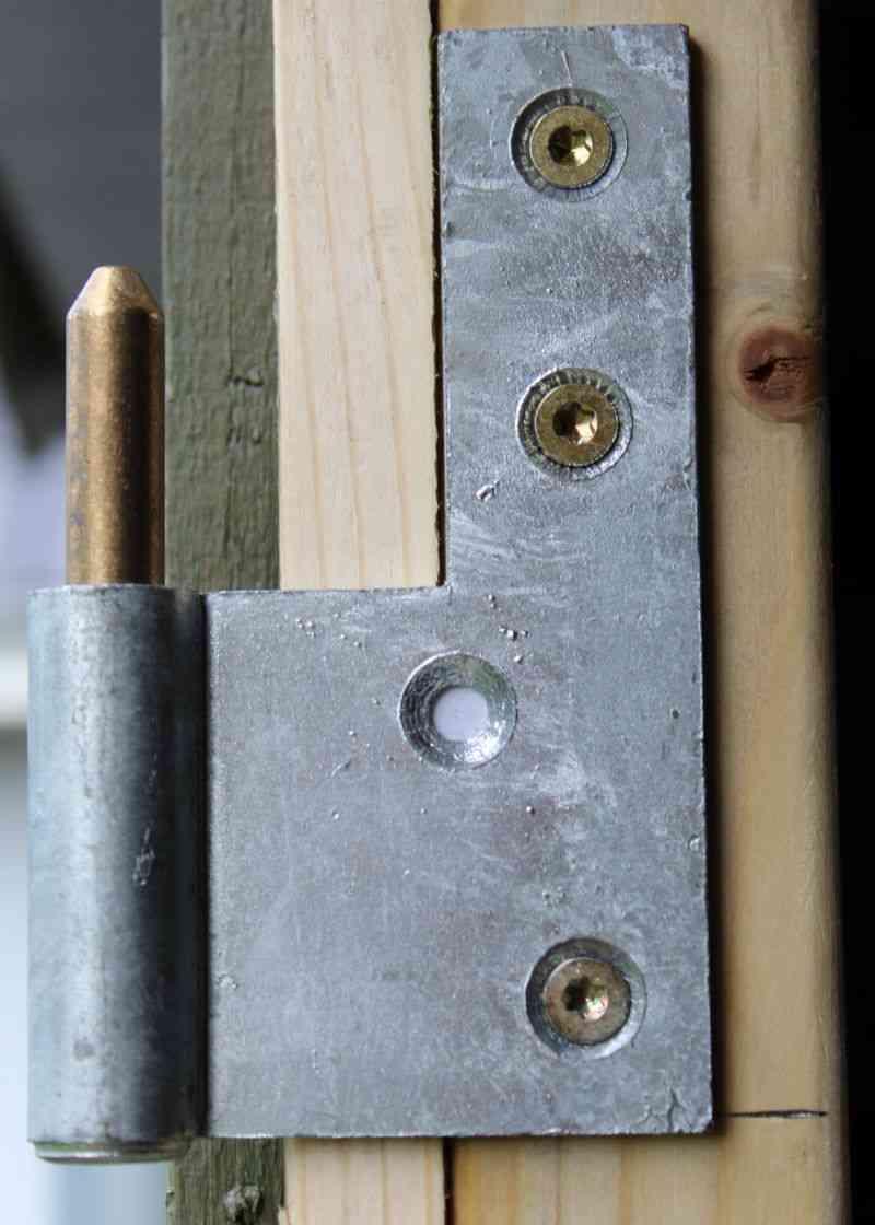 Hængsel monteret på dørstolpe for dør til skur